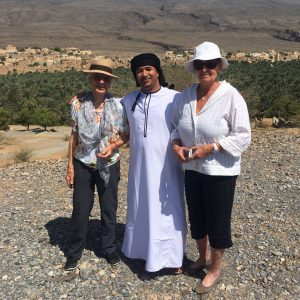 Abdullah in traditional omani dress with two female tourists