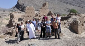 A group of tourists in front of a ruined building in Tanuf