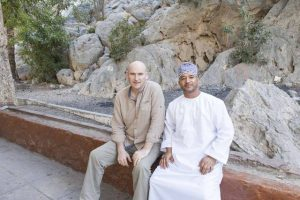 Abdullah Alraisi in traditional omani dress sits with a European man at by the filaj system at wadi bani khalid