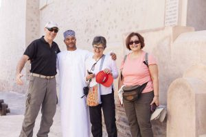 Abdullah Alraisi in traditional omani dress with a group of european tourists at Nakhl fort