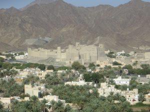 Bahla fort with palm trees in the foreground and Jebel Shams in the background