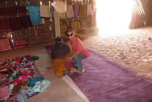 Two female tourists sit on the floor of a Bedouin House one of them dressed in traditional Bedouin clothing