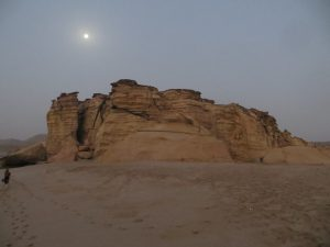 The moon can be seen above a rock formation at Ras Al Jinz Turtle reserve just before sunrise