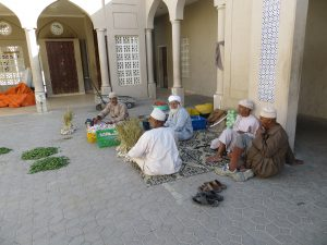 A group of men in traditional Omani dress sit on the ground outside Nizwa souk selling vegetables