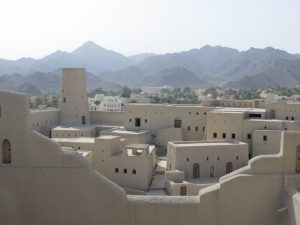 Walls and buildings of Bahla fort with Al Hajar mountains in the background