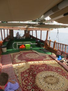 The deck of a traditional dhow with a central carpet and seating cushions around the edge