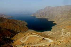 A winding road descends the hillside to a deep blue fjord in Musandam