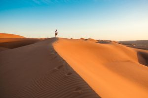 A lone man is standing at the top of a sand dune