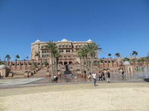 The front entrance to Emirates Palace Hotel with palm trees and fountains in front of the staircase
