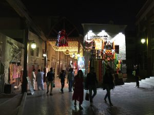 An alleyway in Deira souq at night. A group of people stand in front of a stall selling pashminas