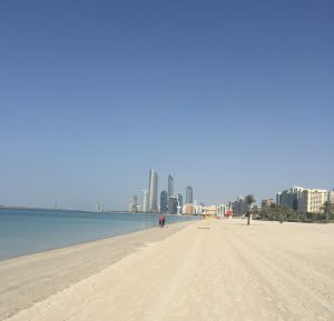 A vast expanse of empty white sand beach with the calm blue sea on the left and the city skyscrapers in the distance