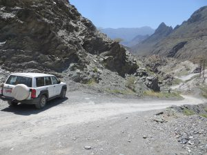 A white 4 is parked at the top of a steep track in Wadi Bani Awf