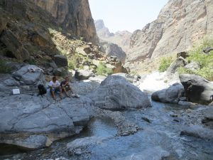 Abdullah Al Raisi sits on a rock in Snake Canyon with a male tourist having a picnic lunch